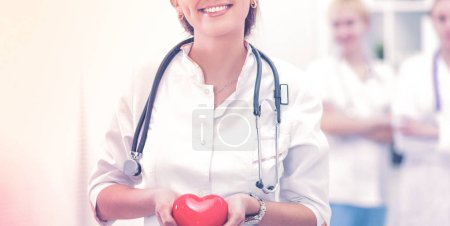 Photo for Female doctor with stethoscope holding heart, isolated on white background - Royalty Free Image