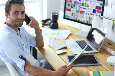 Photo pour Portrait de jeune designer assis dans un studio graphique devant un ordinateur portable et un ordinateur tout en travaillant en ligne - image libre de droit