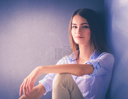 Portrait of a casual happy woman sitting on the fl...