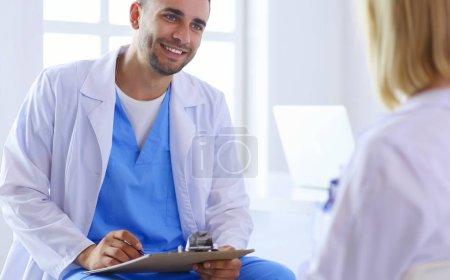 Photo pour Beau médecin parle avec une jeune patiente et prend des notes alors qu'il est assis dans son bureau. - image libre de droit