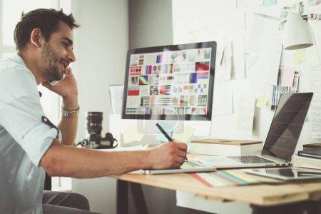 Porträt eines jungen Designers, der im Grafikstudio vor Laptop und Computer sitzt, während er online arbeitet.