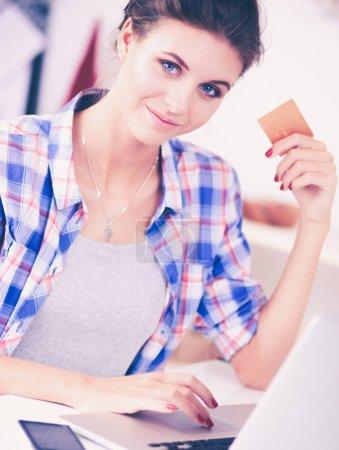 Photo pour Femme souriante, magasinage en ligne à l'aide d'ordinateur et la carte de crédit dans la cuisine. Femme souriante. - image libre de droit