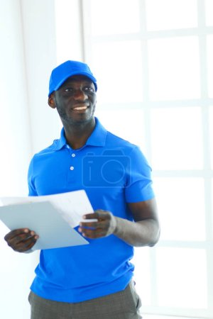 Portrait of an handsome happy deliverer with folder