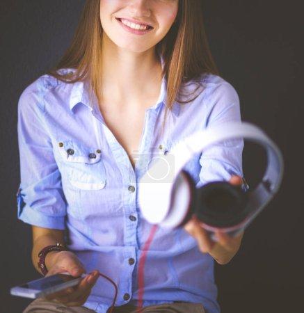 Photo pour Jeune fille heureuse assis sur le plancher et l'écoute de musique. - image libre de droit