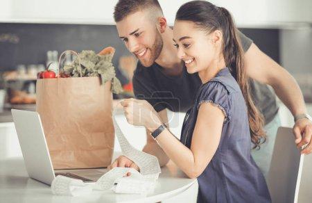 Photo pour Couple payer leurs factures avec ordinateur portable dans la cuisine à la maison . - image libre de droit