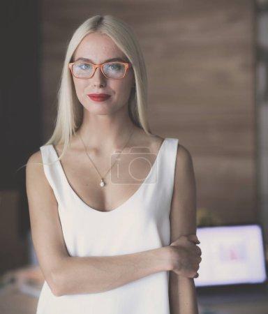 Photo pour Portrait d'une femme d'affaires mature professionnelle exécutive assise sur le bureau - image libre de droit