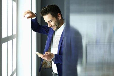 Photo pour Homme d'affaires en costume parlant au téléphone et regardant loin près de la fenêtre - image libre de droit