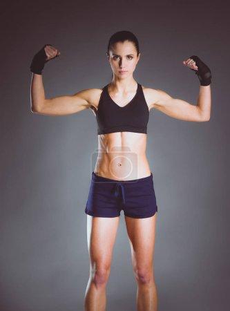 Photo pour Musclé jeune femme posant en vêtements de sport sur fond noir - image libre de droit