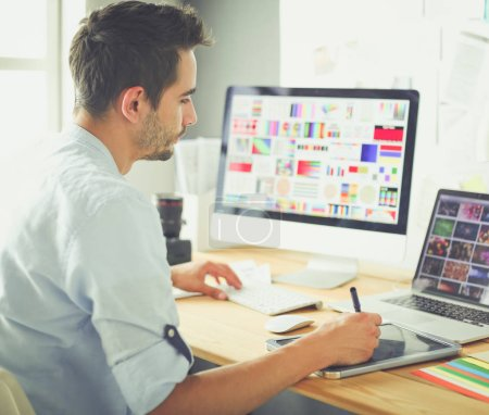 Photo for Portrait of young designer sitting at graphic studio in front of laptop and computer while working online - Royalty Free Image