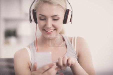 Photo pour Portrait de la belle jeune femme à la maison assis sur le canapé et écoute de musique - image libre de droit