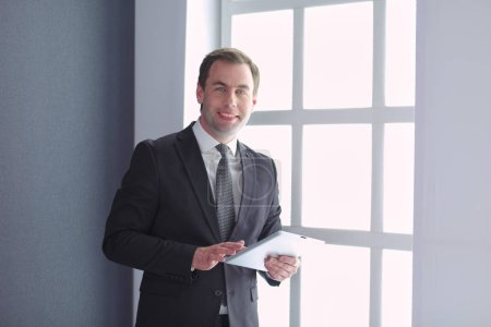 Photo for Portrait of young businessman in office with big window. Businessman using tablet computer and looking at camera - Royalty Free Image