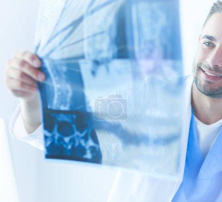 Photo pour Jeune docteur assis à son bureau et l'analyse de la radiographie. - image libre de droit
