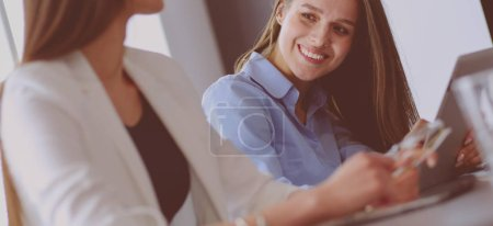 Photo for Two female colleagues in office sitting on the desk. - Royalty Free Image