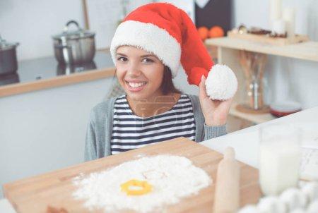 Photo pour Femme au chapeau de Père Noël faire des biscuits de Noël dans la cuisine. - image libre de droit