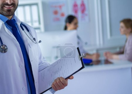 Photo for Smiling doctor man standing in front of his team and patient. - Royalty Free Image