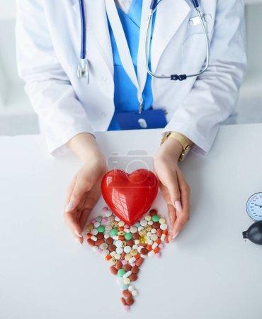 Photo pour Cardiologue avec coeur rouge et stéthoscope à table. - image libre de droit