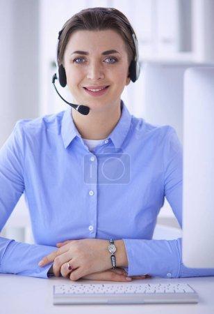 Photo pour Sérieuse jolie jeune femme travaillant comme opérateur de téléphonie de soutien avec casque au bureau. - image libre de droit