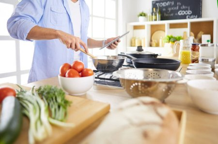 Photo for Man following recipe on digital tablet and cooking tasty and healthy food in kitchen at home. - Royalty Free Image
