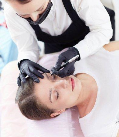 Photo pour Cosmetologue appliquant un maquillage permanent sur les sourcils . - image libre de droit