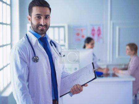 Photo pour Homme de docteur de sourire restant devant son équipe et patient. - image libre de droit