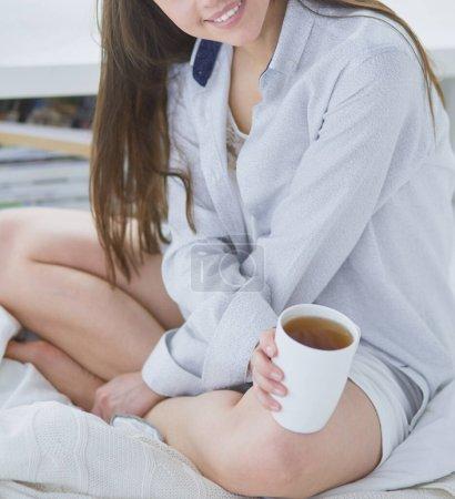 Photo pour Femme assise au lit lisant un livre et prenant le petit déjeuner . - image libre de droit