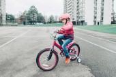 """Постер, картина, фотообои """"Портрет улыбающейся кавказской дошкольникки верхом на розовом велосипеде на велосипеде в шлеме на заднем дворе дороги снаружи в весенний осенний день. Концепция сезонной детской деятельности. Здоровый детский образ жизни"""""""