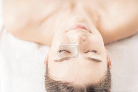 Photo pour Visage détendu de jeune femme allongée dans un salon de beauté - image libre de droit