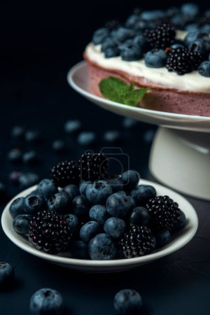 Plate with blackberry and blueberry, cottage cheese casserole on the dark textured background.