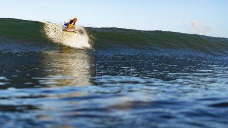 Photo pour Jeune athlète masculin nageant sur une planche de surf dans l'océan à Nusa Dua Beach, Bali, Indonésie. - image libre de droit