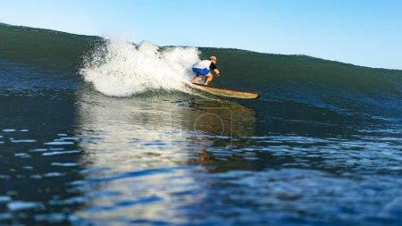 Foto de Joven atleta masculino nadando en tabla de surf en el océano en Nusa Dua Beach, Bali, Indonesia. - Imagen libre de derechos
