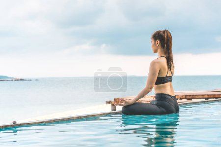 Photo for Vacation of Beautiful Attractive Asian woman relaxing in yoga lotus pose on the pool above the beach with beautiful sea in Tropical island,Feeling comfortable and relax in holiday,Vacations Concept - Royalty Free Image