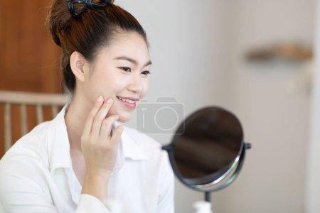 Photo pour Portrait d'une beauté jeune femme brune cosmétiques regardant dans le miroir avec une peau fraîche et saine du visage, se sentant si frais et heureux, Beauté et Cosmétiques Concept - image libre de droit