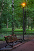 Glowing lantern in a summer evening park, underneath a bench for relaxation and a walkway