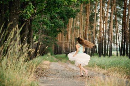Photo pour Une petite fille aux cheveux longs danse dans la forêt en jupe pleine . - image libre de droit