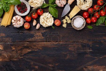 Photo pour Italien ingrédients alimentaires fond. Spaghettis, tagliatelles, basilic, parmesan, tomates, ail sur une vieille table rustique en bois, vue sur le dessus, espace pour copier - image libre de droit