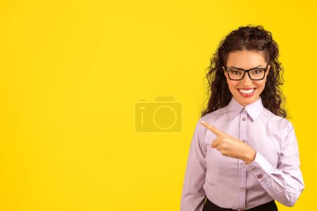 Young formal woman in eyeglasses smiling at camera and pointing away on bright yellow backdrop.
