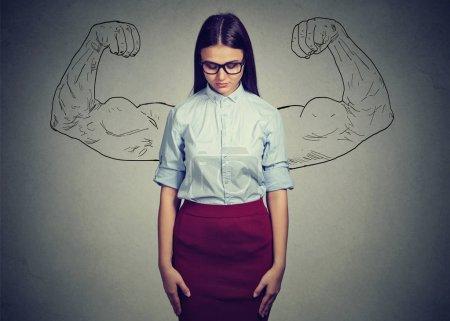 Mujer joven y elegante mirando hacia abajo tener problemas con la autoestima y la incredulidad en la fuerza de uno mismo