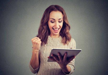 Photo pour Joyeux femme mignonne dans la tenue poing vers le haut heureux avec succès tout en utilisant la tablette sur fond gris . - image libre de droit