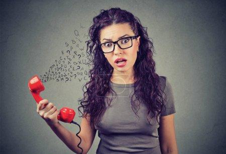 Photo pour Choqué jeune femme traitant avec quelqu'un impoli au téléphone - image libre de droit