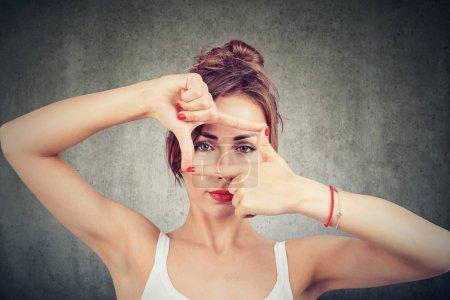 Jeune fille faisant cadre avec les doigts et regardant à travers les limites de la caméra sur fond gris