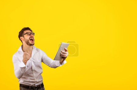 Photo pour Gai lumineux hipster homme tenant poing vers le haut tout en criant avec bonheur de gagner sur fond jaune et tenant tablette - image libre de droit