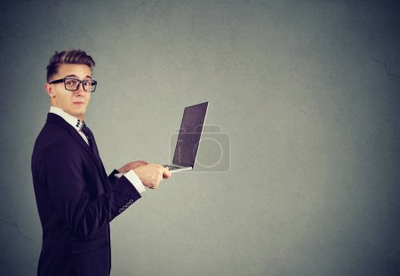 Photo for Side view of offended formal young man in suit holding laptop in dislike and looking at camera with annoyance - Royalty Free Image