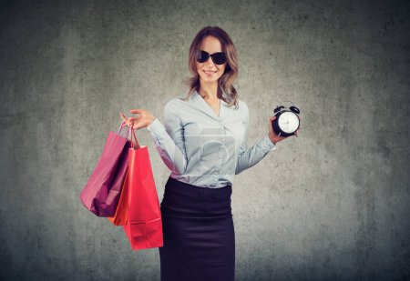 Photo for Stylish woman holding shopping bags and alarm clock showing time for sales and discounts on gray background - Royalty Free Image
