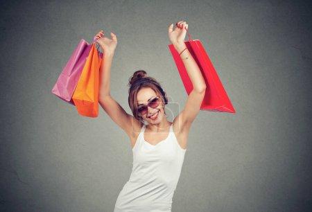 Photo pour Femme moderne gaie dans des lunettes de soleil et des écouteurs tenant des sacs en papier coloré dans la main levée heureux avec des achats - image libre de droit