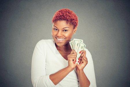 Photo pour Portrait d'une jeune femme super heureuse et enthousiaste tenant à la main des billets en dollars, isolée sur fond gris. Concept de récompense financière - image libre de droit