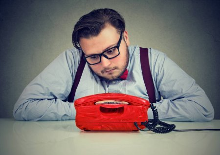 Photo for Desperate sad man waiting for someone to call him - Royalty Free Image