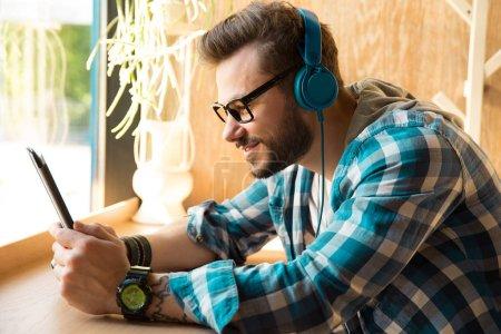 Photo pour Vue latérale de l'homme décontracté dans un casque tablette de surf assis dans un café à la table - image libre de droit