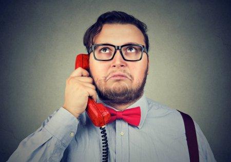 Photo pour Adulte gros homme en noeud papillon rouge et lunettes parlant au téléphone levant les yeux dans la perplexité - image libre de droit