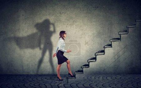 Foto de Super héroe mujer de negocios subiendo escaleras hasta el éxito sobre fondo gris de la pared - Imagen libre de derechos