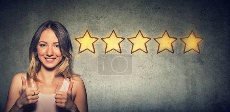 Photo pour Joyeux beau sourire femme montrant pouce vers le haut comme geste en choisissant cinq étoiles notation. Excellent concept de service client . - image libre de droit